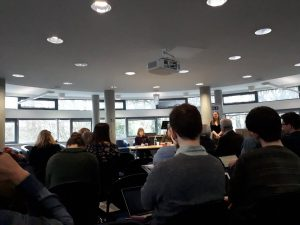 """Photograph of presentations part of the third panel, """"Voices, Books and Musical Effects'. Panel members are seated at the far side of a modern seminar room with the seated backs and back of heads of the attendees listening to them in the foreground"""