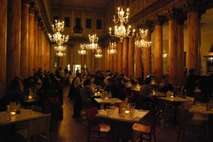 Photograph of ballroom style resturant venue with ornate columns and chandelier light fittings. People sit at tables in three rows up and down the floor